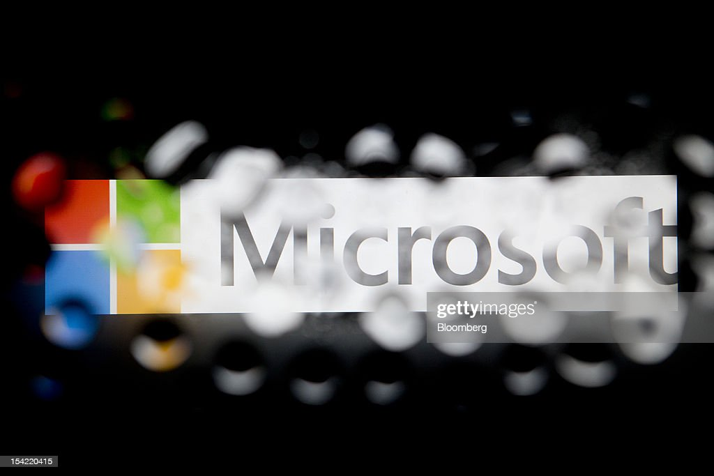 The Microsoft Corp. logo is seen through water droplets for an arranged photograph in Washington, D.C., U.S., on Monday, Oct. 15, 2012. Microsoft Corp. is scheduled to release earnings data on Oct. 18. Photographer: Andrew Harrer/Bloomberg via Getty Images
