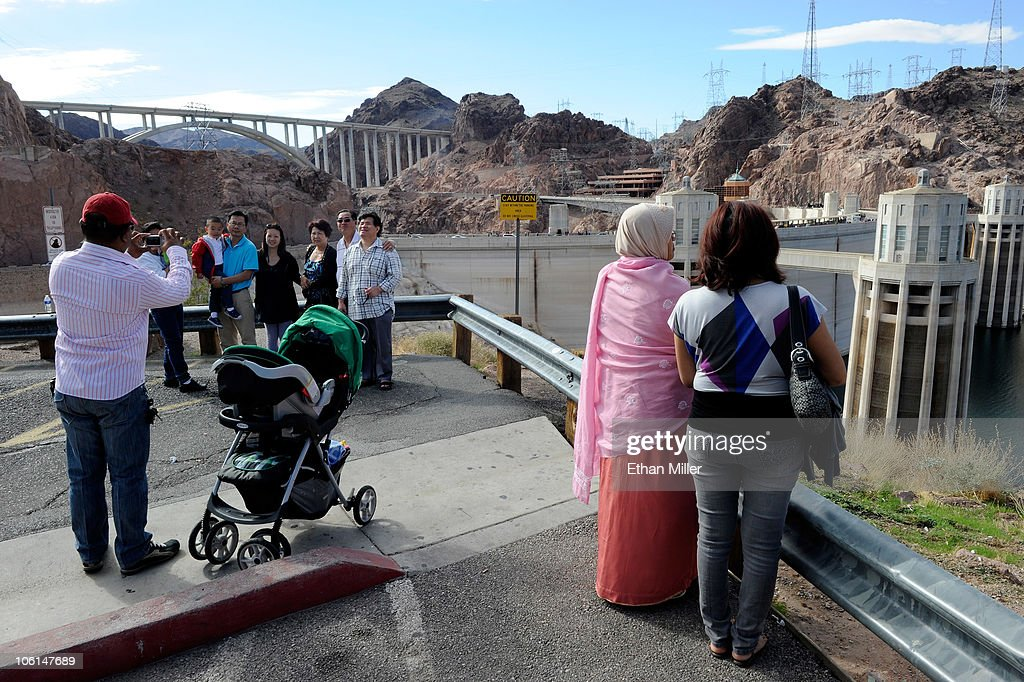 The Mike O'Callaghan-Pat Tillman Memorial Bridge part of the Hoover Dam Bypass Project is visible behind tourists visiting the Hoover Dam October 26, 2010 in the Lake Mead National Recreation Area, Arizona. The 1,900-foot-long structure sits 890 feet above the Colorado River, about a quarter of a mile downstream from the Hoover Dam. The USD 240 million four-lane bypass project to relieve vehicle traffic on the Hoover Dam began in 2003, and opened to traffic on October 19.