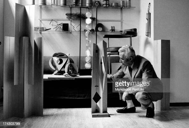 The Milanese designer Bruno Munari in his studiohe's working on a poster with his surname Milan June 1969