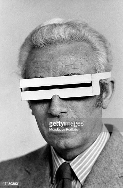 The Milanese designer Bruno Munari poses for the photographer with a rake in his hand and surrounded by plant on the balcony of his house in Milan...