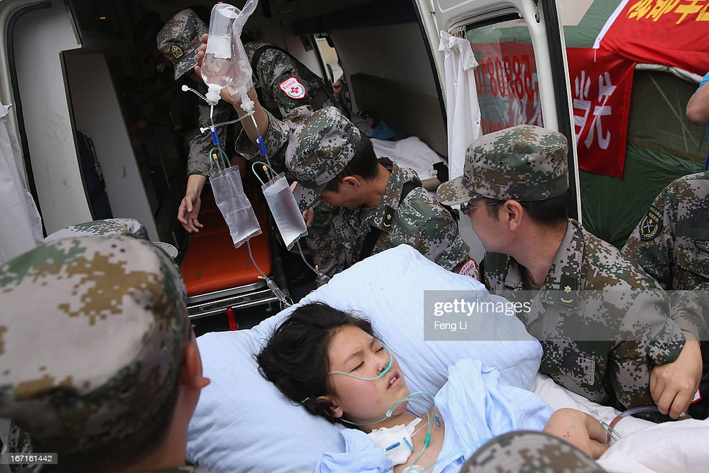 The military medical officers carry a patient to an ambulance at the hospital on April 22, 2013 in Lushan of Ya An, China. A magnitude 7 earthquake hit China's Sichuan province on April 20 claiming over 180 lives and injuring thousands.