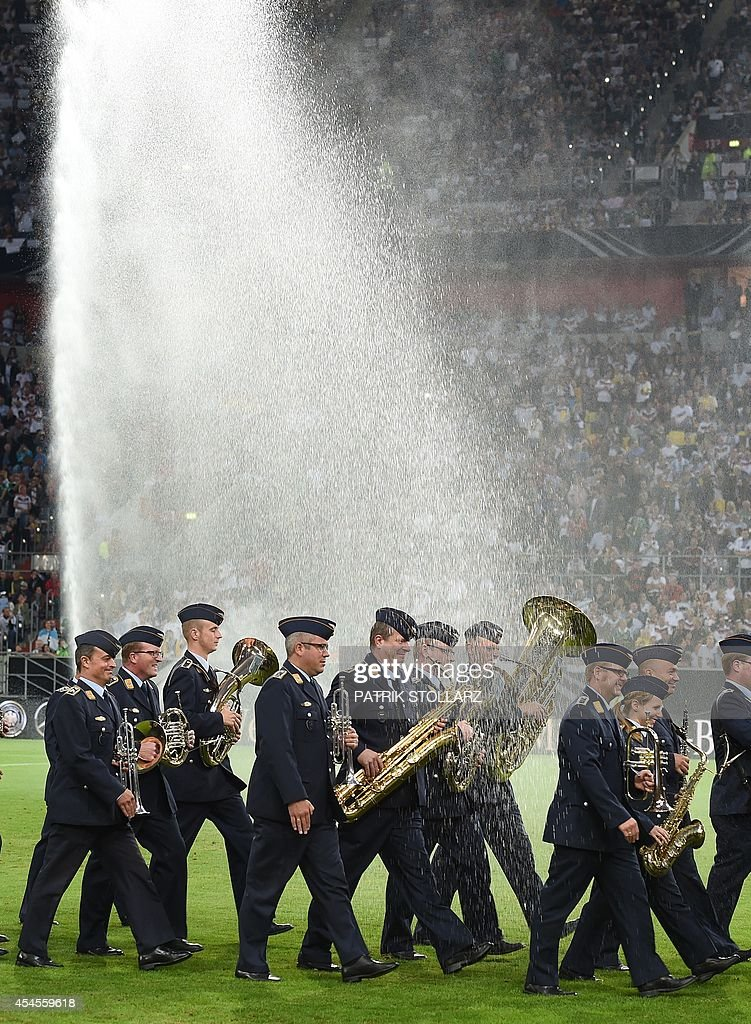 The military orchester group walk through the a water fontain prior to a friendly football match between Germany vs Argentina in Duesseldorf, Germany, on September 3, 2014.
