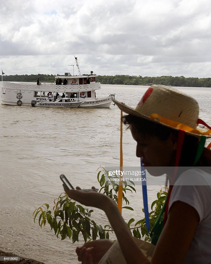 The Military Police patrols the Amazon Bay in front of the Federal University of Para as a woman looks at herself on a mirror during the World Social...