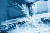 The milling machine cutting the part using  the coolant  with the light blue scene
