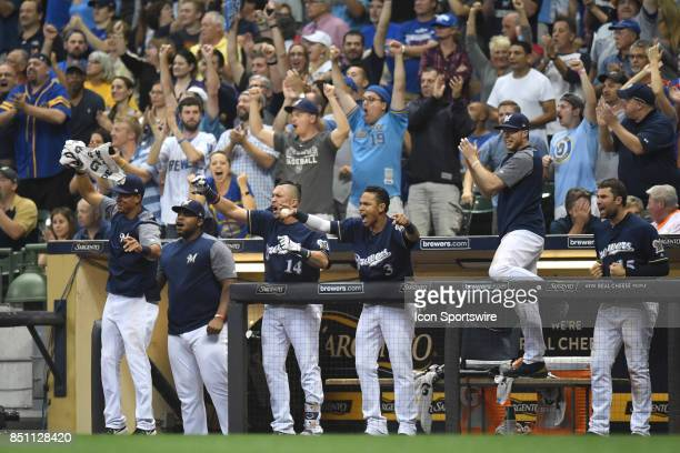 The Milwaukee Brewers bench and left fielder Hernan Perez shortstop Orlando Arcia celebrate after scoring during a game between the and the Chicago...