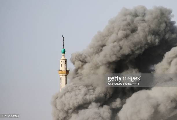 The minaret of a mosque is engulfed by smoke following a reported air strike by Syrian government forces on a rebelheld area in the southern city of...