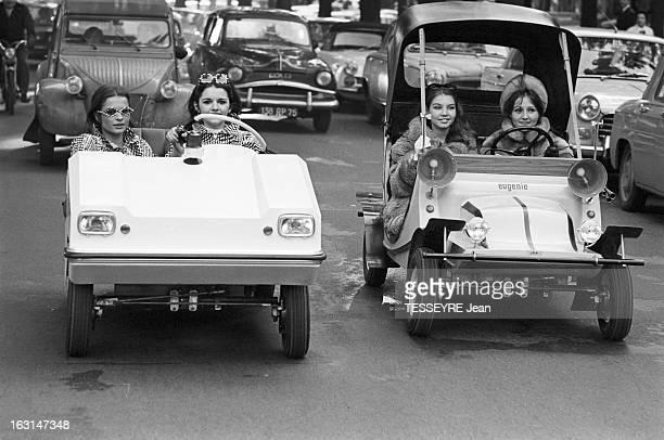The Mini Cars Vogue In Paris En France sur une avenue des jeunes femmes souriantes roulant à bord de de modèles différent de minivoiture La voiture...