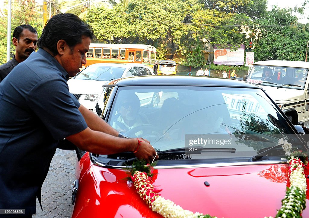 The 'Mini Cooper S' motor car, gifted by Indian Bollywood film actor Abhishek Bachchan to his daughter Aaradhya is driven by her grandfather and film actor Amitabh Bachchan, accompanied by her grandmother and film actress Jaya Bachchan and her mother and film actress Aishwarya Rai Bachchan at Pratiksha Bunglow, Juhu in Mumbai on November 12, 2012.