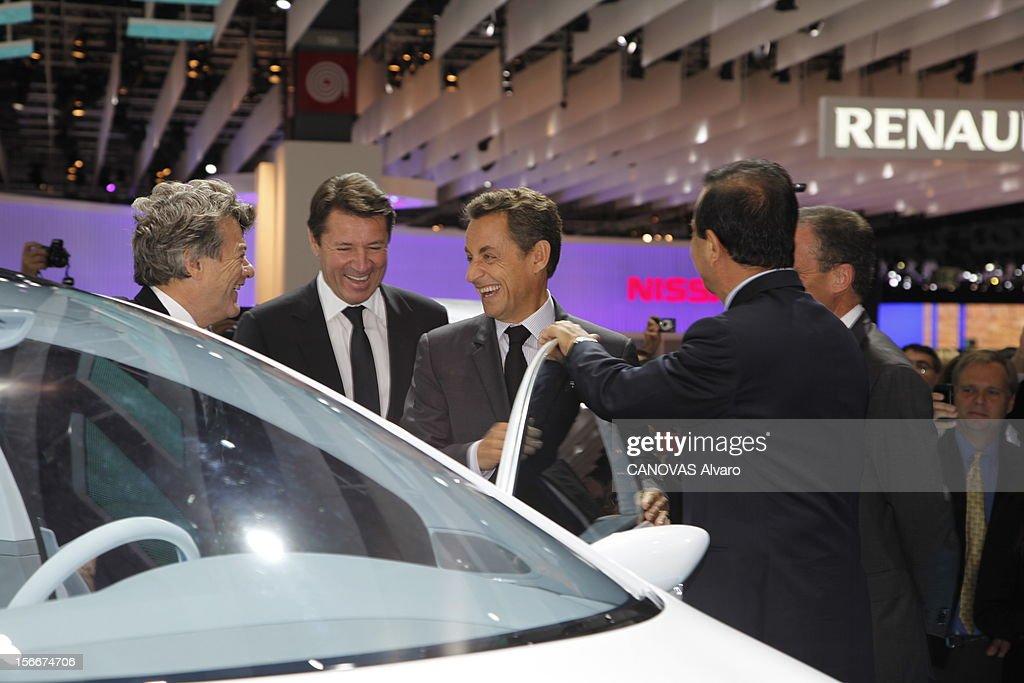 The Minister Of Ecology Jean-louis Borloo. Paris, Vendredi 1er octobre 2010, au Mondial de l'automobile : Jean-Louis BORLOO, ministre de l'Ecologie, de l'Energie, du Développement durable et de la Mer, plaisantant avec Nicolas SARKOZY en présence de Christian ESTROSI, ministre de l'Industrie, et de Carlos GHOSN (de dos), président de Renault, la main sur la portière.