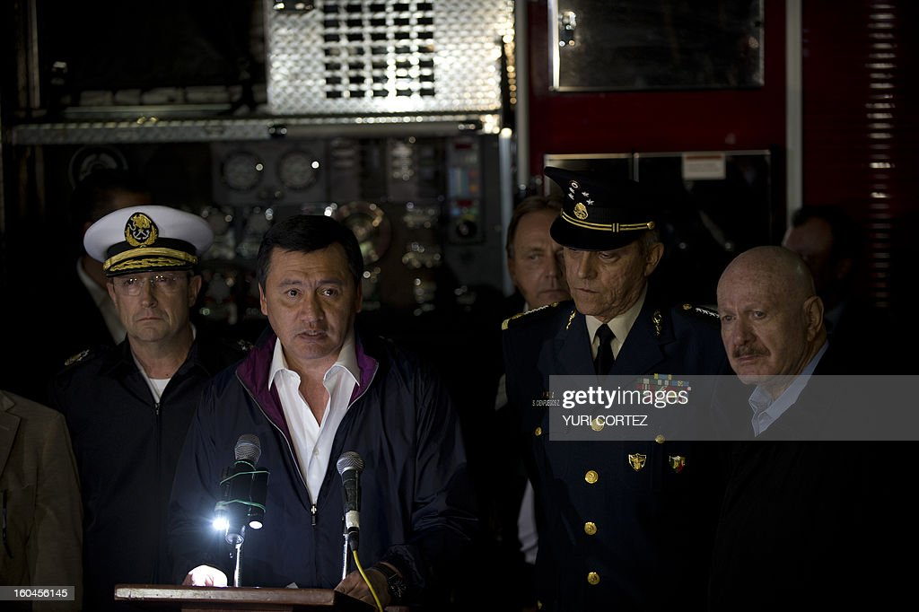The Minister of the Interior, Miguel Angel Osorio Chong (C-L) addresses a press conference at the headquarters of state-owned Mexican oil giant Pemex in Mexico City on January 31, 2013, following a blast inside the building. An explosion rocked the skyscraper, leaving up to 25 dead and 101 injured, as a plume of black smoke billowed from the 54-floor tower, according to official sources.