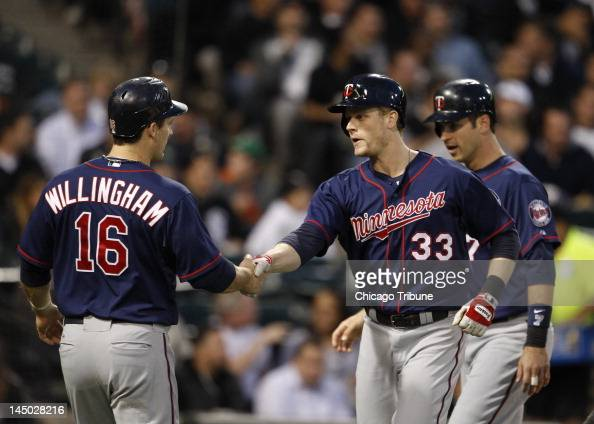 The Minnesota Twins' Josh Willingham congratulates Justin Morneau after his threerun home run against the Chicago White Sox during the fourth inning...