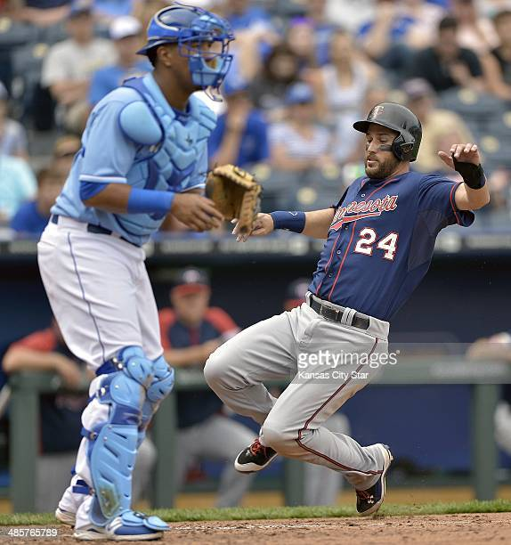 The Minnesota Twins' Trevor Plouffe scores as Kansas City Royals catcher Salvador Perez looks for the throw in the seventh inning at Kauffman Stadium...
