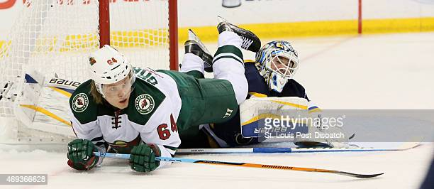 The Minnesota Wild's Mikael Granlun left falls over St Louis Blues goaltender Brian Elliott in the second period on Saturday April 11 at the...