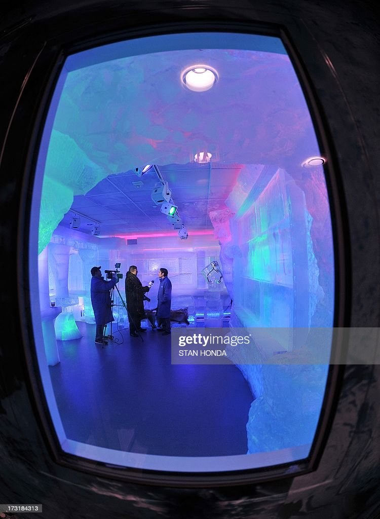 The Minus 5 Ice Bar seen through a window in the entrance door during a preview at the New York Hilton Midtown Hotel July 9, 2013 in New York. The bar is constructed of 90 tons of ice and is kept at a temperature of -5 degrees C (23 degrees F). Guests are given parkas, gloves and hats and for an additional fee, fur coats. Designs in the wall and around the bar are carved by ice sculptor Peter Slavin. AFP PHOTO/Stan HONDA