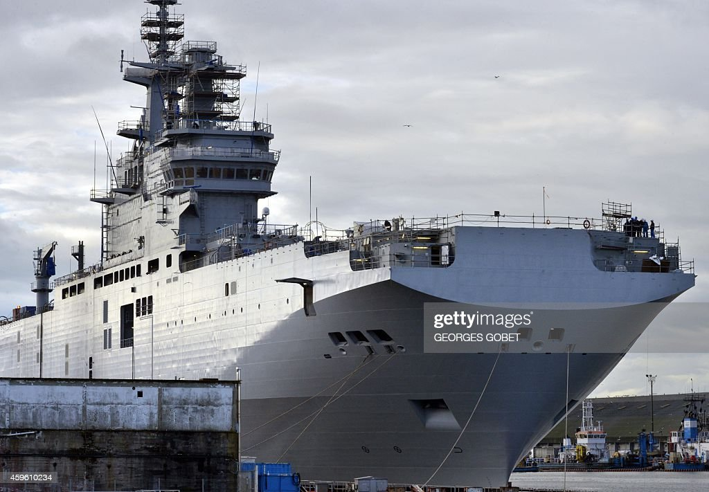 The Mistral-class assault warship Sevastopol, the second of two mammoth Mistral helicopter carriers built for Russia, is docked on November 26, 2014 in the western French port of Saint-Nazaire after being taken from its dry dock on November 20. France on November 25 pushed back 'until further notice' the delivery of the first of the two ships, the Vladivostok warship, to Russia because of the Ukraine crisis, sparking a measured initial response from Moscow. The Vladivostok was supposed to be delivered to Russia on November 15, according to the original deal signed in 2011 and worth 1.2 billion euros ($1.5 billion) for both vessels. France however faces huge penalties if it breaches the 1.2 billion euro ($1.5 billion) contract.