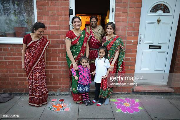 The Mistry family pose outside their home after decorating the pavement with sand known as rangoli art to celebrate the Hindu festival of Diwali on...