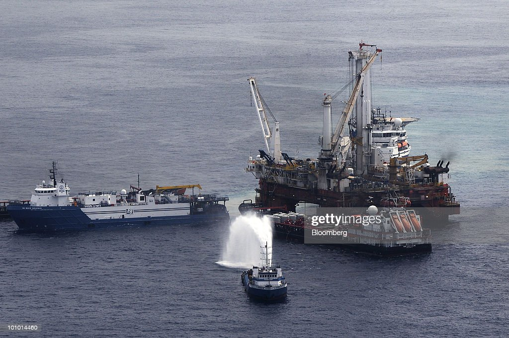 The mobile offshore drilling unit Q4000, right, holds position directly over the damaged Deepwater Horizon blowout preventer as crews work to plug the wellhead using a technique known as 'top kill' in the Gulf of Mexico, on Wednesday, May 26, 2010. BP Plc temporarily stopped the flow from the leaking Macondo well in the Gulf of Mexico, indicating progress on its plans to plug a well that's been spewing oil for more than a month, U.S. Coast Guard Admiral Thad Allen said. Photographer: Patrick Kelley/U.S. Coast Guard via Bloomberg