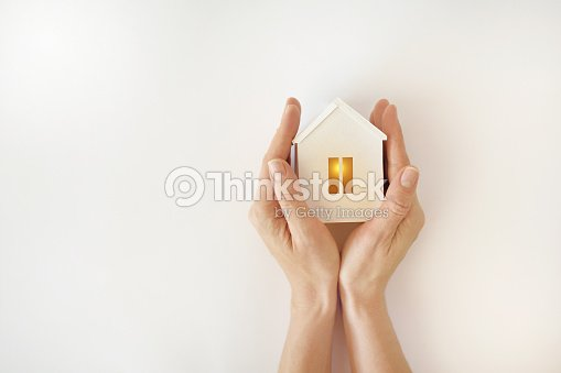 The model of the White House with warm light inside in female hands on a white background : Stock Photo
