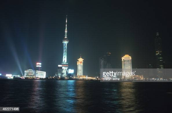 The modern architecture of Pudong Shanghai's financial district across the Huangpu river from The Bund is lit up at night