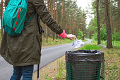 The modern woman throwing out garbage in trash basket, environmental conservation, protecting the nature.