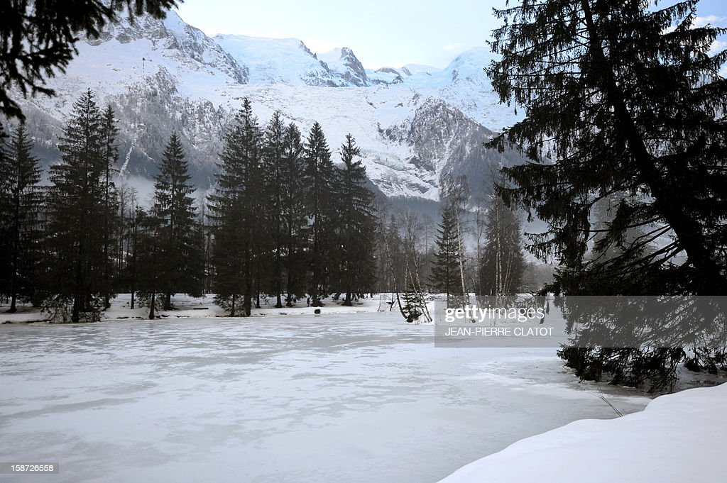 The Mont-Blanc mountain chain and the Bossons glacier are pictured on December 26, 2012 behind the frozen Gailland lake in the Chamonix valley, French Alps. AFP PHOTO / Jean Pierre Clatot