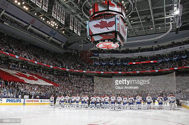 The Montreal Canadiens and the Toronto Maple Leafs stand during the anthem prior to the NHL season opener at the Air Canada Centre on October 8 2014...