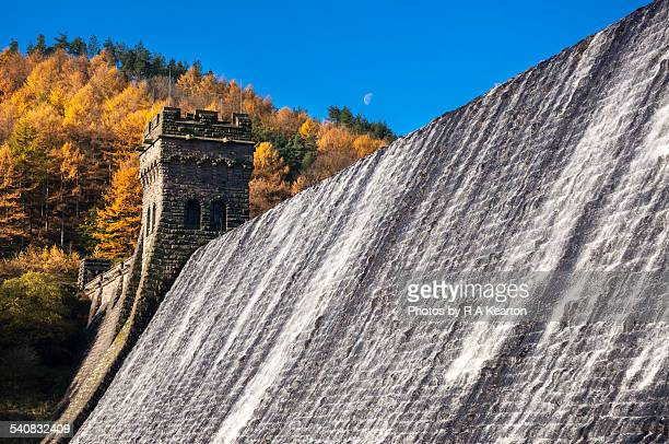 The moon above Derwent dam on a sunny autumn day