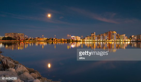The moon and cityscape lights, reflect off harbour waters, poole : Stock Photo