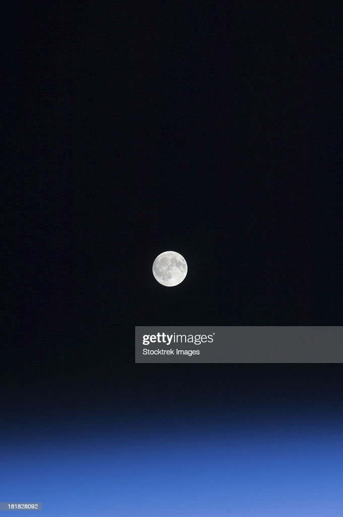 The moon and Earth's atmosphere as seen from the International Space Station over a period of time that covered a number of orbits by the orbital outpost.