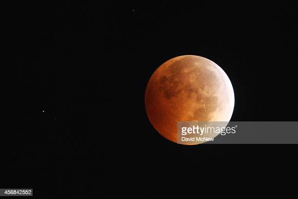 The moon is illuminated by sunlight reflected off the Earth during a total lunar eclipse one of four socalled 'blood moons' on October 8 2014 in Los...