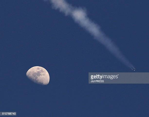 The moon is seen as an H2A rocket carrying the ASTROH satellite developed in collaboration between the Japan Aerospace Exploration Agency NASA and...