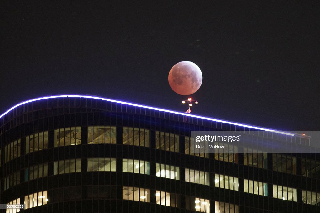 The moon is seen behind downtown highrise buildings during the shortest total lunar eclipse of the century before dawn on April 4 2014 in Los Angeles...