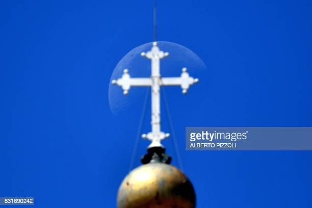 The moon is seen behind the cross of the dome of St Peter's Basilica as Pope Francis addresses the crowd from the window of the apostolic palace...