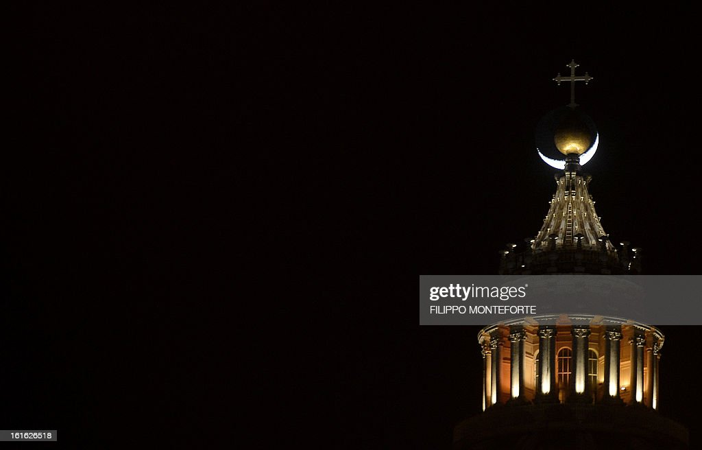 The moon is seen behind the cross on the top of Saint Peter's dome at the Vatican on February 13, 2013. Pope Benedict XVI made his first public appearance today since his shock resignation announcement, asking thousands of cheering pilgrims at the Vatican to 'keep praying for me'.