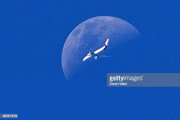 The moon makes a impressive background for a plane flying over Auckland