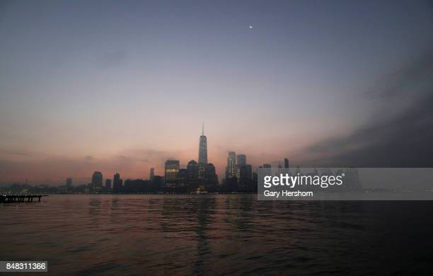 The moon rises at sunrise over lower Manhattan and One World Trade Center in New York City on September 16 as seen from Jersey City NJ