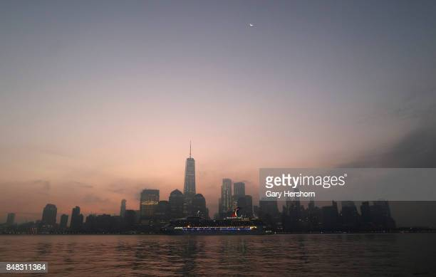 The moon rises at sunrise over lower Manhattan as a cruise ship passes One World Trade Center in New York City on September 16 as seen from Jersey...
