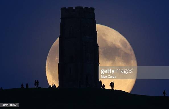 The moon rises over people gathered on Glastonbury Tor on July 31 2015 in Somerset England The full moon appearing on July 31 is what is called a...