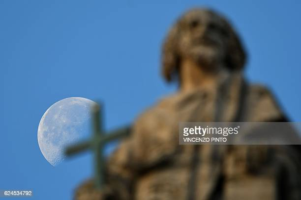 TOPSHOT The moon sets behind a statue of St Peter's basilica before a holy mass for the closing of the Jubilee of Mercy on November 20 2016 at St...