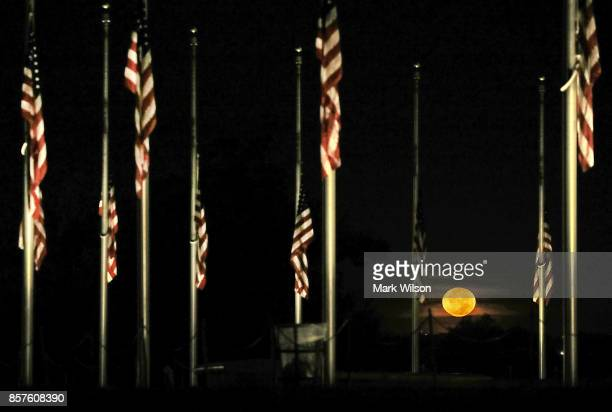 The moon sets beyond the American flags on the grounds of the Washington Monument have been lowered to halfstaff on October 4 2017 in Washington DC...