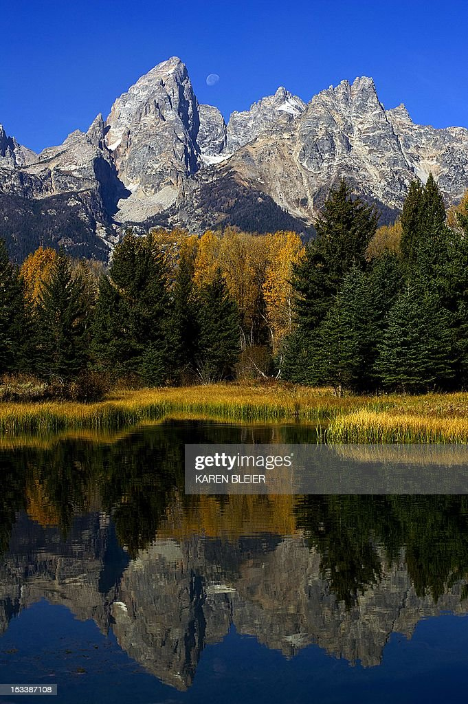 The Moon sets next to the Grand Teton October 4 2012 in the Grand Teton National Park in Wyoming Grand Teton National Park is located in northwestern...