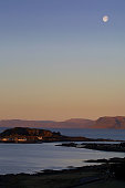 The moon setting over the inner Hebridean islands of Mull and Easdale as seen from the neighbouring island of Seil on Scotland's rugged and...