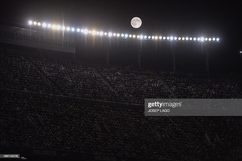 The moon shines during the Spanish league football match FC Barcelona vs Malaga CF at the Camp Nou stadium in Barcelona on August 29 2015 AFP PHOTO/...