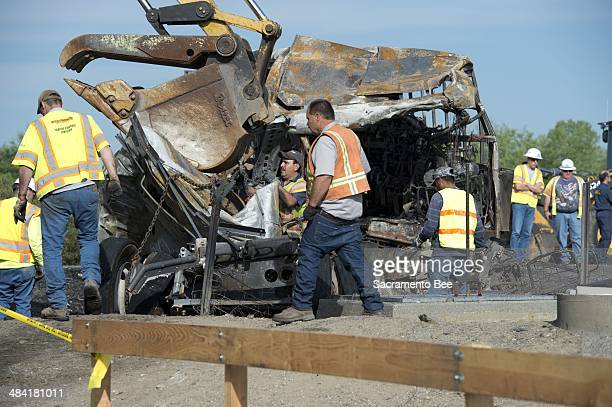 The morning after the accident Fri April 11 Caltrans workers begin clearing the charred remains of a charter bus that collided with a FedEx tractor...