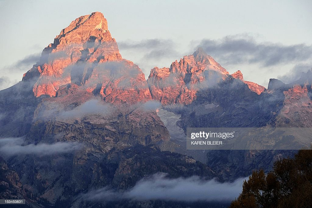 The morning Sun hits the tips of the Grand Tetons on October 5 2012 in the Grand Teton National Park in Wyoming Grand Teton National Park is located...