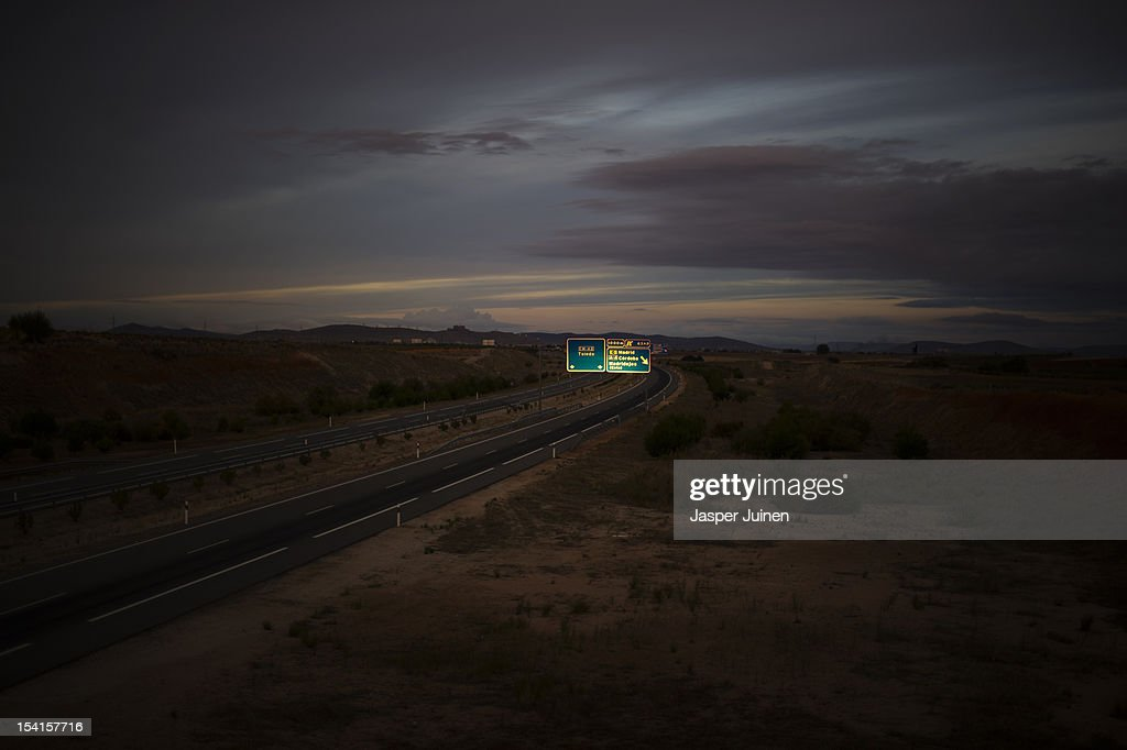 The morning sun reflects in a roadsign above a newly contructed empty high way stretching through the windswept La Mancha countryside on October 12, 2012 in the direction of the small industrial town of Villacanas, Spain. During the boom years, where in its peak Spain built some 800,000 houses a year, more than Britain, Germany and France combined, and millions of wooden doors where needed, the people of Villacanas were part of a proud elite enjoying high wages and permanent jobs. Almost all of those doors used came from this small industrial town in the La Mancha province, some seven million a year, leaving with truck loads at the same time, from the now empty and silent Villacanas industrial park. With Spain in recession and the housing bubble busted, the door industry is shattered and unemployment in Villacanas, zero for nearly a generation, is rising fast.