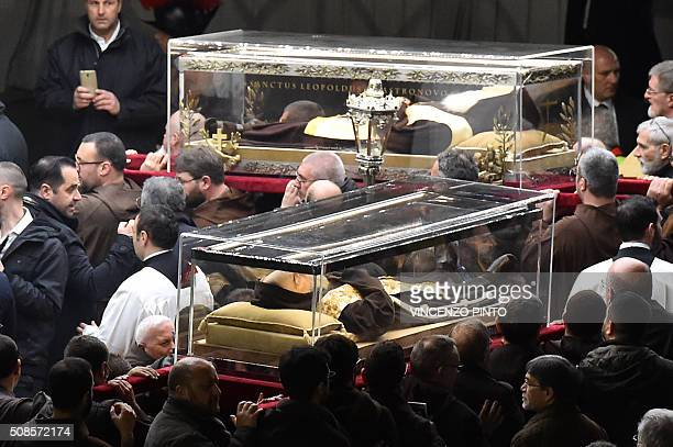 The mortal remains of St Pius of Pietrelcina Padre Pio bottom and St Leopold Mandic arrive in procession at St Peter's basilica on February 5 2016 in...