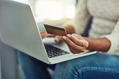 Shot of an unrecognizable woman making payments online with a credit card at home