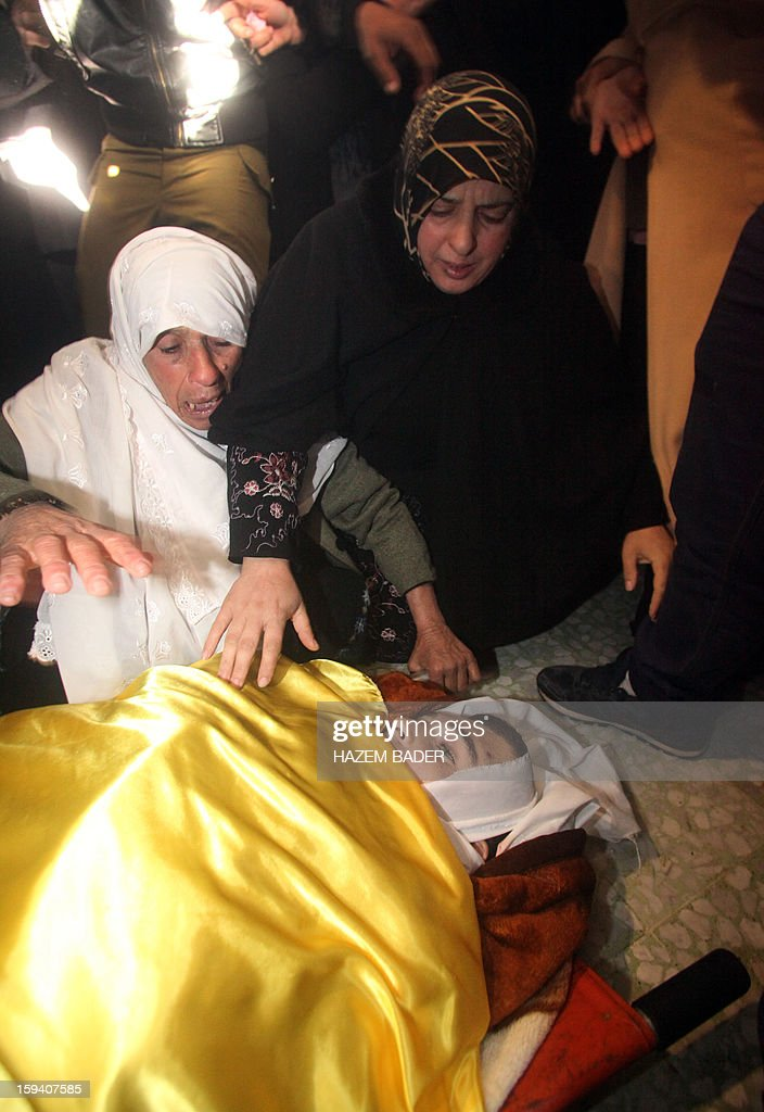 The mother (R) and another woman mourn over the body of Odai Darwish, 21, on January 13, 2013, in the village of Duma, the day after he was shot dead by Israeli soldiers as he tried to sneak from the occupied West Bank, south of the city of Hebron, into the Jewish State to get to a job, Palestinian officials told AFP. The Israeli military confirmed that a border shooting took place but did not know the extent of the man's injuries.