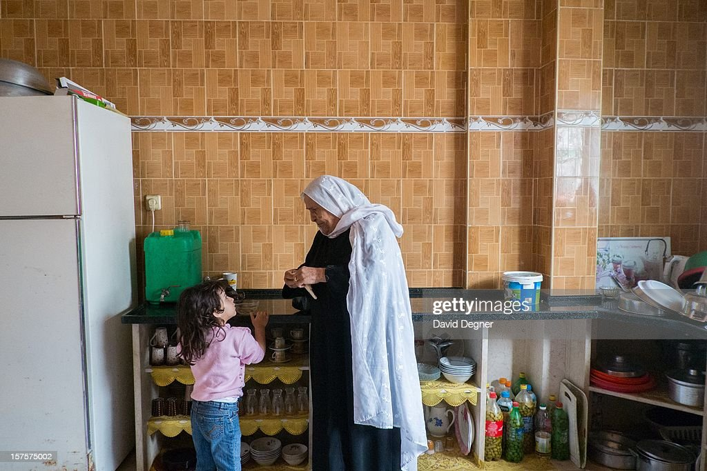 The mother and daughter of Said Ibrahim Abu Rial prepare to leave their house for the evening in the Shati Refugee Camp in Gaza on November 21, 2012. They are often without electricity so all the food in their fridge has gone bad. During the day the family mainly stays in their home, without electricity, but at night they retreat to another apartment in a safer area. Photo by David Degner/Getty Images)